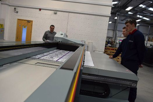 Leroy Fox, Sales Director of Contract Sign Systems (left) and two employees watch the new Océ Arizona 6160 XTS in action