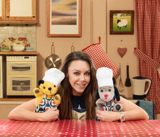 "Michelle Heaton with Sooty & Sweep.  ""Orla Kiely has created a limited edition apron for Sport Relief available from HomeSense and TK Maxx stores"""