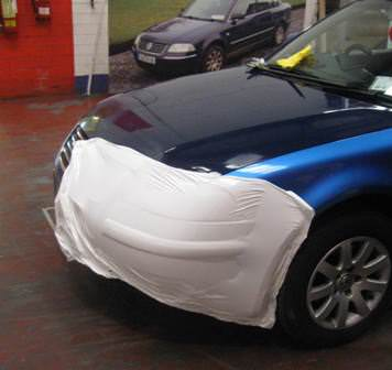 The original car in the background with part of the new colour wrap in fron
